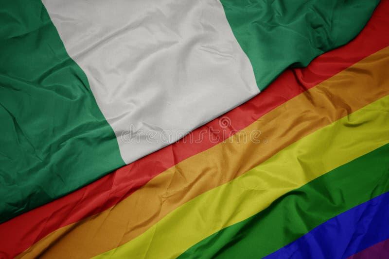 machać kolorową homoseksualną tęczy flagę i flagę państowową Nigeria zdjęcie stock