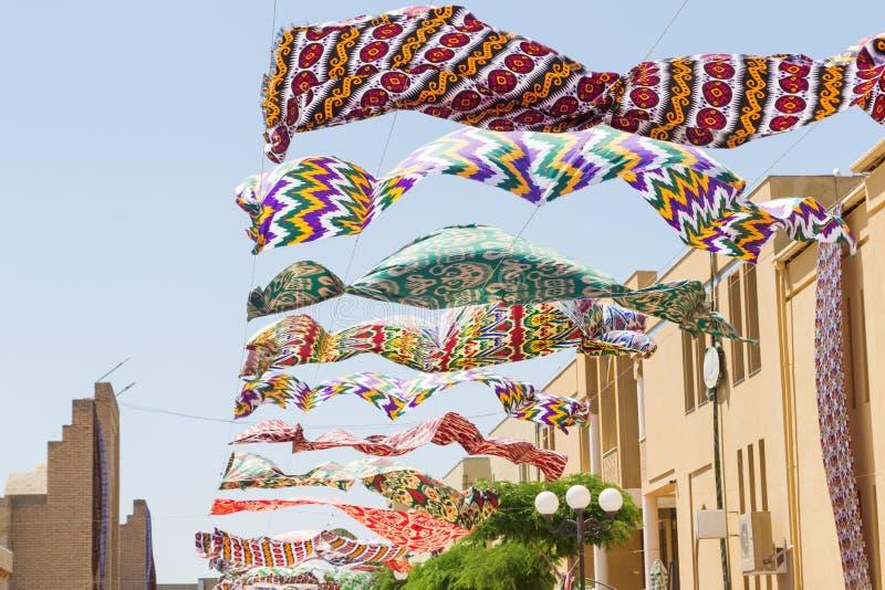 Machać w niebo tkaninie Stubarwni jedwabniczy tekstylni materiały trzepocze przeciw niebieskiemu niebu Girlanda jaskrawy barwiony zdjęcie stock