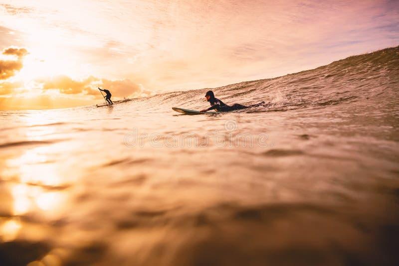 Macha w oceanie przy zmierzchem lub wschodem słońca z surfingowami Wodny sport w oceanie fotografia stock