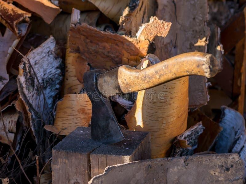 Machado colado em um início de uma sessão a jarda sobre um woodpile na rua imagens de stock