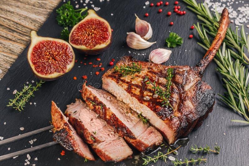 Machado de guerra grelhado cortado da costeleta de carne de porco na placa da ardósia com figos fotos de stock