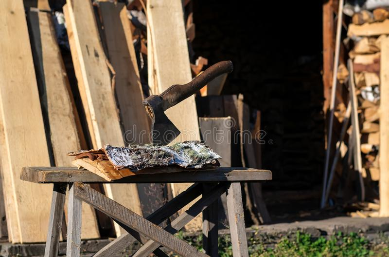 Machado empurrado em uma casca de vidoeiro em um log perto do woodpile fotografia de stock