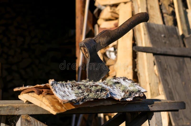 Machado empurrado em uma casca de vidoeiro em um log perto do woodpile foto de stock royalty free