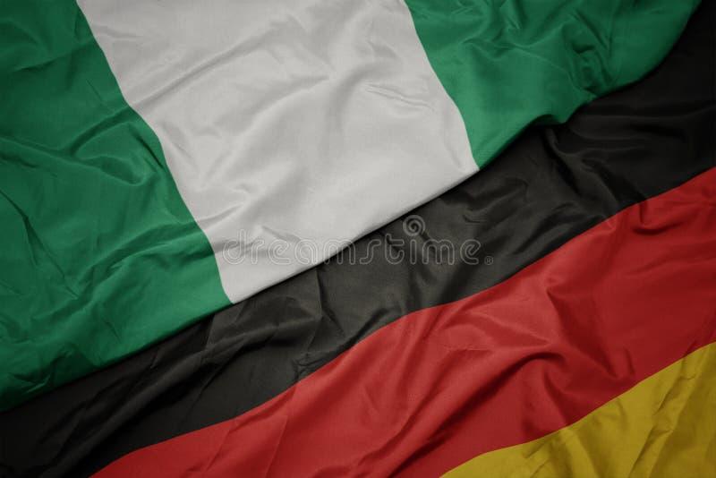 machajÄ…c kolorowÄ… flagÄ… Niemiec i narodowej flagi Nigerii zdjęcie stock
