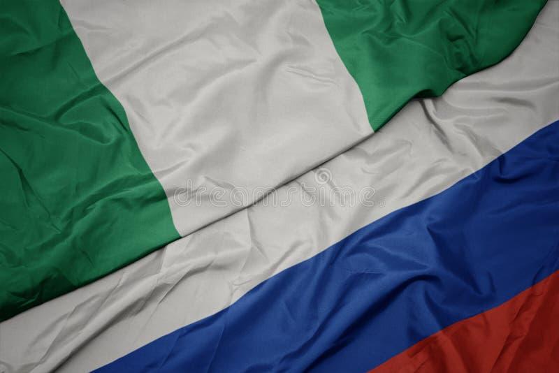 machajÄ…ca kolorowÄ… flagÄ… Rosji i narodowÄ… flagÄ… Nigerii zdjęcia royalty free