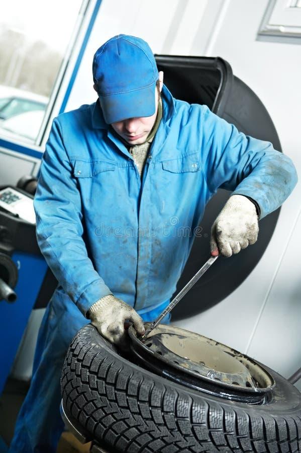 Machanic Schlosser am Reifenbeschlag stockfoto