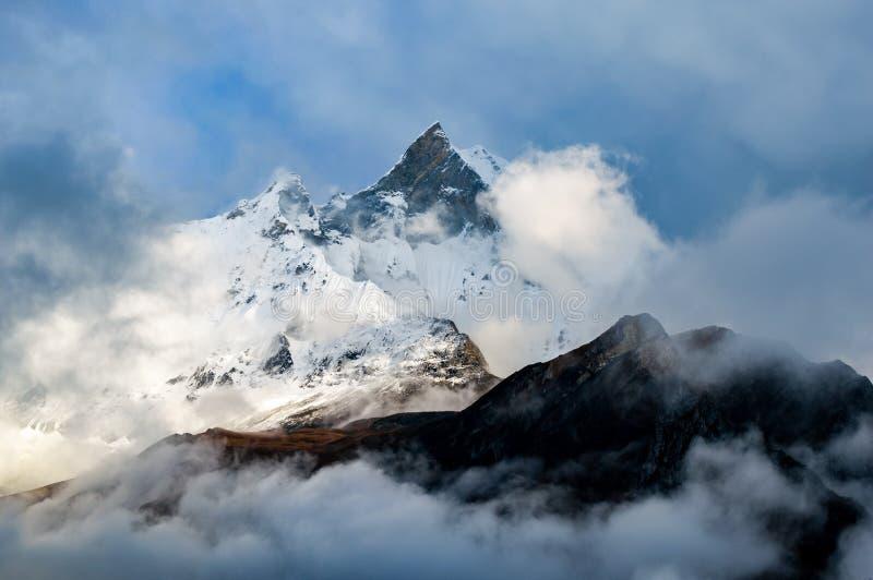 Machapuchare,鱼尾巴山上升在从安纳布尔纳峰营地足迹的云彩上的,尼泊尔 免版税图库摄影