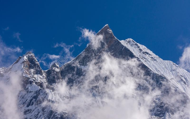 Machapuchare snowcapped mountain summit rises among the clouds, Nepal stock image