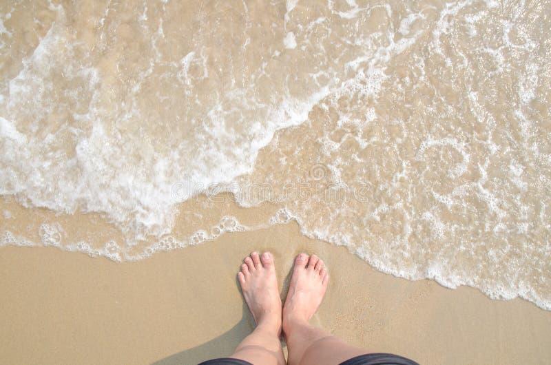 Machen Sie auf Sommerozeanstrand, Füße auf Meersand mit Blasenflosswelle Urlaub stockfoto