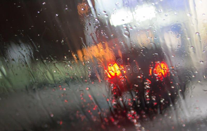 Machen Sie das Fenster mit Hintergrund der Nachtstadtverkehrsansicht nass stockbild