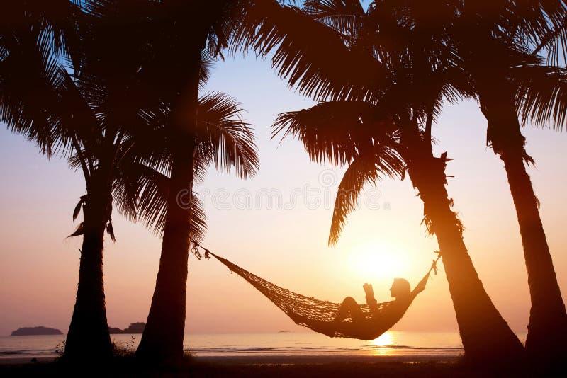 Machen Sie in der Hängematte auf schönem Sonnenuntergangstrand, Feiertagskonzept Urlaub lizenzfreie stockbilder
