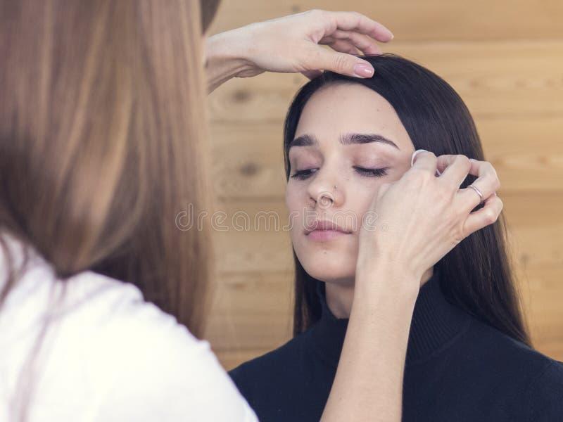 Machen Sie korrekte Augenbrauen aus attraktives brunette Frauenschwarzkleid, das im runden Spiegellicht, Make-uphintergrund, Schö lizenzfreie stockfotos