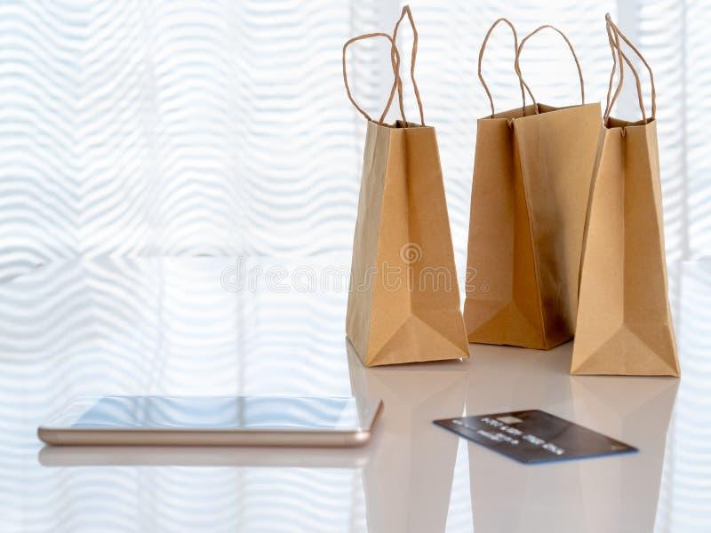Machen Sie Pakete mit Käufen, Smartphone, Kreditkarte auf Tabelle in Handarbeit stockfoto