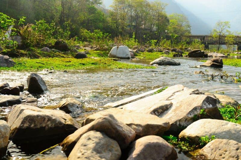 Machen Sie ringsum Felsen auf einem Riverbank mit Gras im Hintergrund glatt lizenzfreie stockbilder