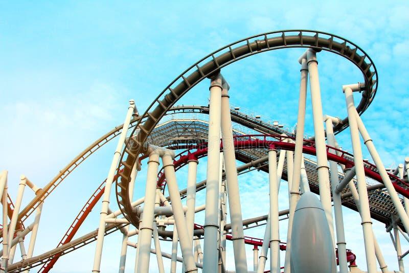 Machen Sie Urlaub und genießen Sie concep, Rote und weiße Stahlachterbahn im Vergnügungspark mit hellem blauem Sommerhimmel stockfotografie