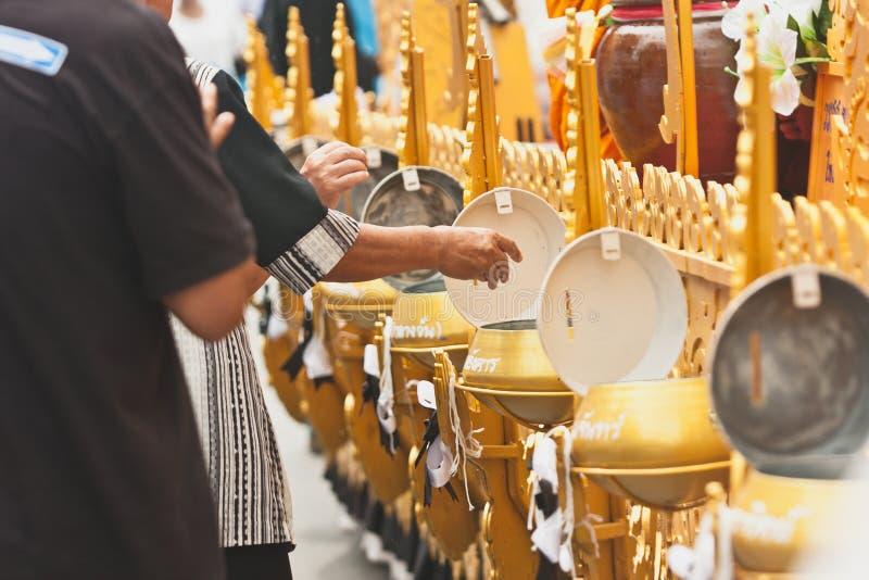 Machen Sie Verdienst und geben Sie den buddhistischen Mönchen Lebensmittelangebote oder spenden Sie Geld am Ende von buddhistisch lizenzfreie stockfotografie