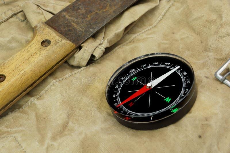 Machette et boussole magnétique sur le sac à dos superficiel par les agents image libre de droits