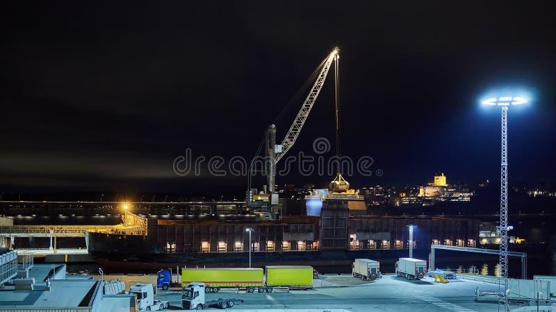 Machinalni hydrauliczni clamshell chciwowie ładuje węgiel na statku przy nocą zdjęcia stock