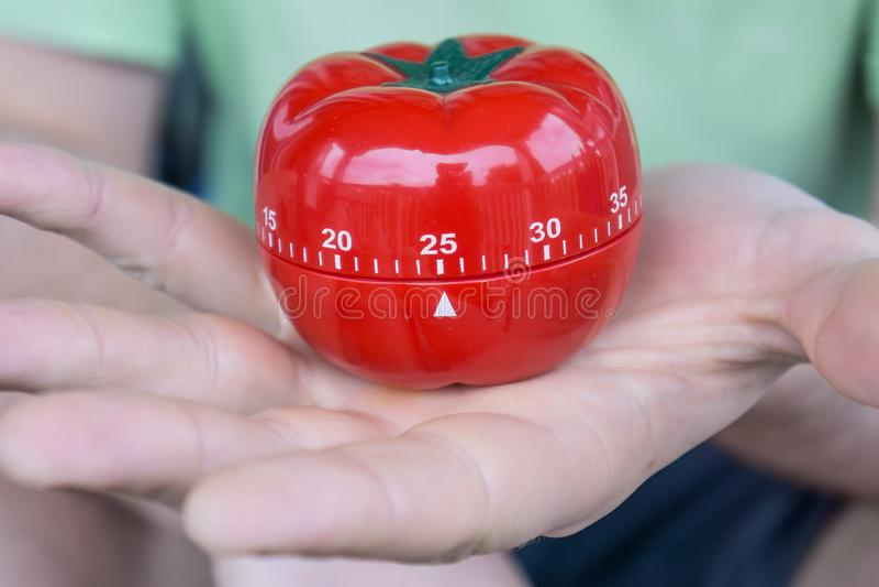 Machinalny czerwony pomidorowy kuchenny zegar ustawiający 25 jeden otwartą ręką, trzymający zdjęcie royalty free