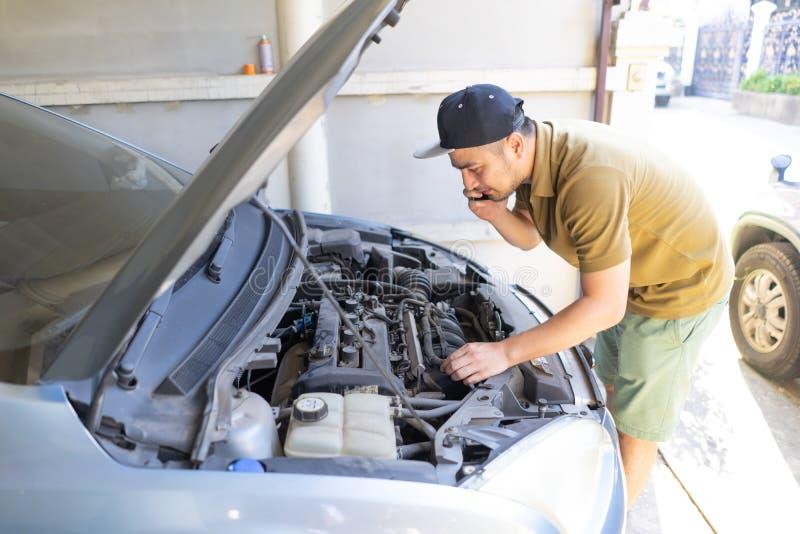 Machinalny naprawianie samochód w domu Naprawiać Usługową radę telefonem komórkowym Mechanik, technika mężczyzna sprawdza samocho zdjęcie stock