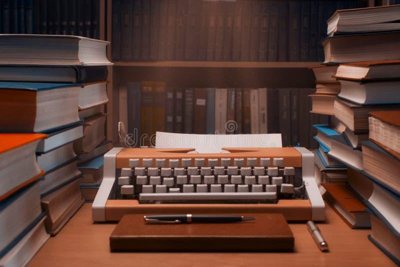 Machine à écrire avec la page du papier blanche avec beaucoup de livres dans le backgrou images libres de droits