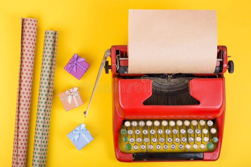 machine à écrire rouge avec le papier vide de métier, boîte-cadeau sur le fond jaune photo libre de droits