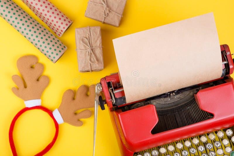 machine à écrire rouge avec le papier vide de métier, boîte-cadeau sur le fond jaune images stock