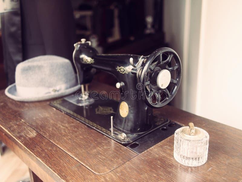 Machine à coudre allemande de vieux cru sur une table en bois avec un chapeau photo stock