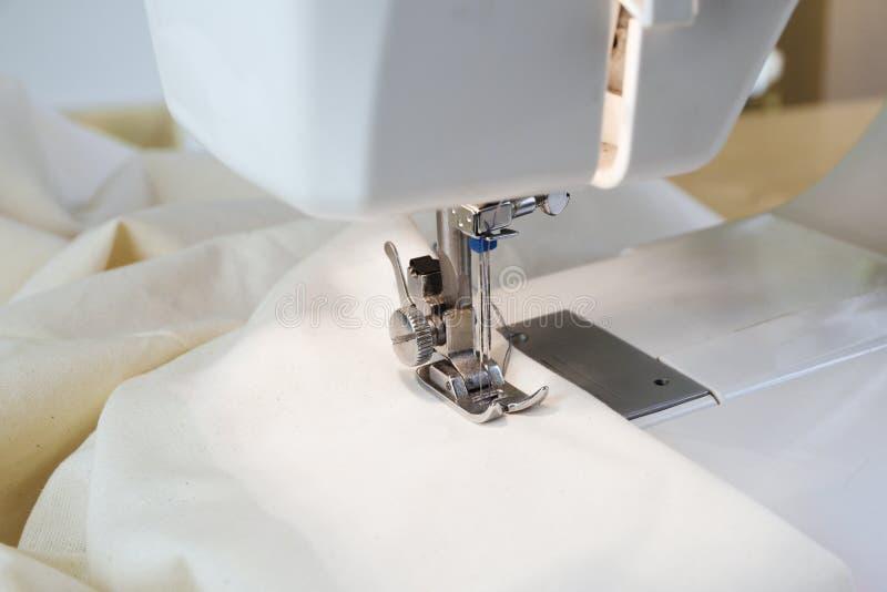 Machine à coudre avec le tissu blanc sous l'aiguille et le presse images stock