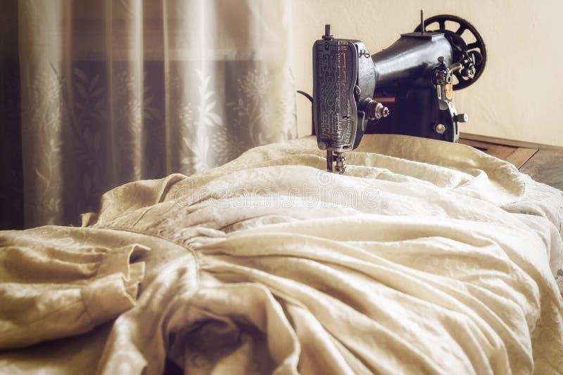 Machine à coudre de cru avec une vieille robe de jeune mariée photographie stock