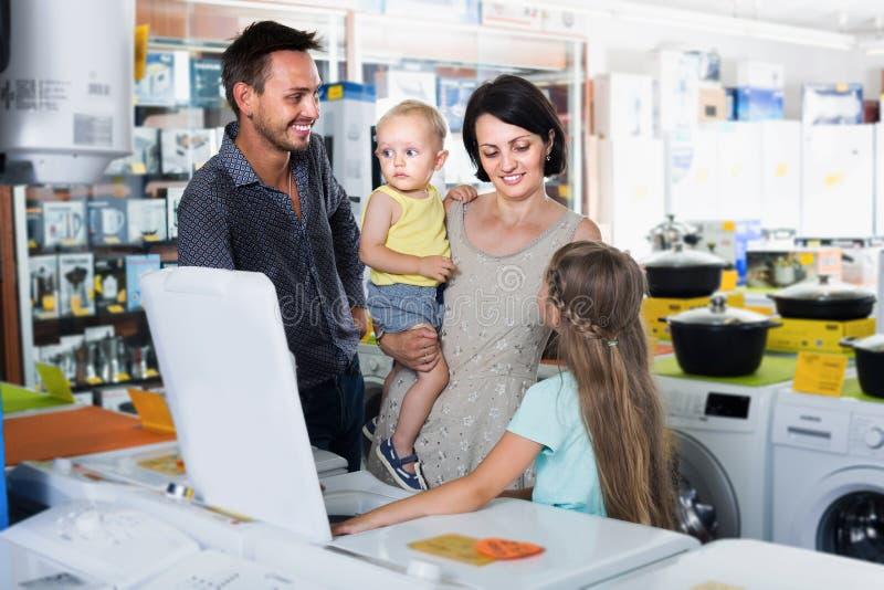 Machine à laver d'achats de famille dans la section de vente au détail de ménage image stock