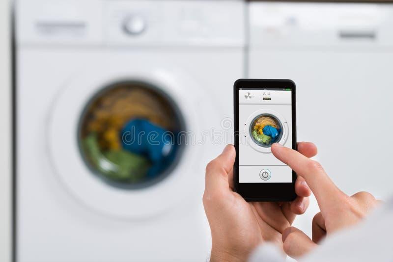 Machine à laver fonctionnante de Person Hands With Mobile Phone photos libres de droits