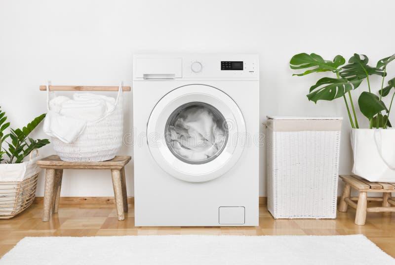 Machine à laver moderne, blanchisserie dans les paniers et intérieur domestique de pièce photos stock