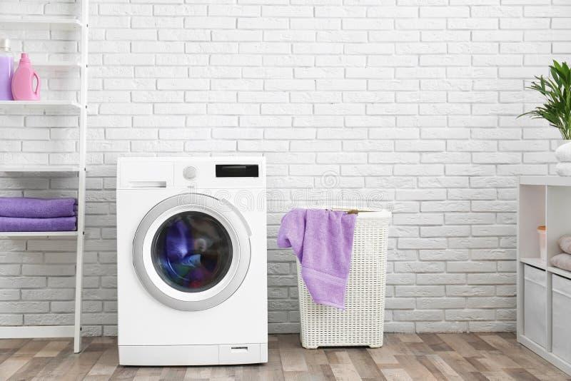 Machine à laver moderne près de mur de briques dans l'intérieur de buanderie photographie stock libre de droits