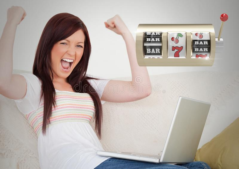 Machine à sous de casino devant la femme jouant sur l'ordinateur portable image libre de droits