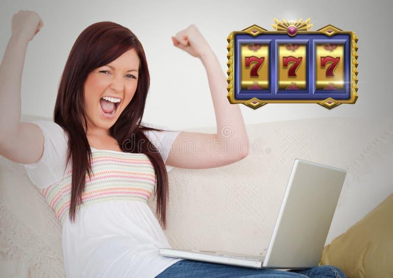 Machine à sous de casino 7's devant la femme célébrant jouer sur l'ordinateur portable images libres de droits