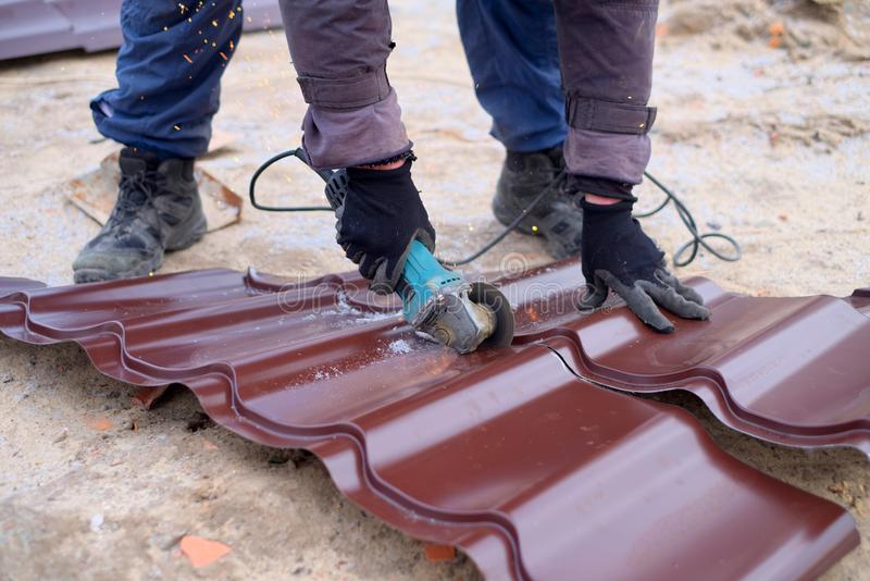 Machine de meulage d'utilisation de travailleur pour la coupure de la feuille de toiture en métal photographie stock libre de droits