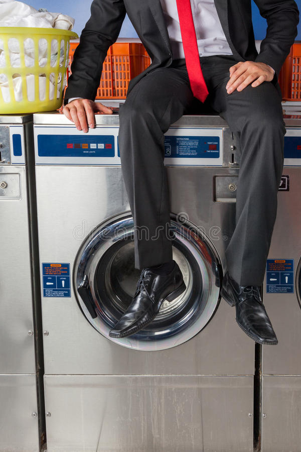 Machine de Sitting On Washing d'homme d'affaires photographie stock libre de droits