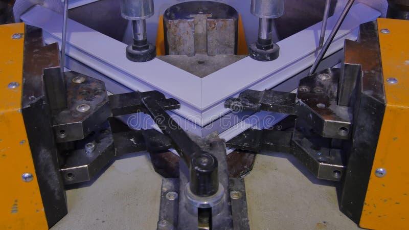 Machine de soudure fonctionnante de travailleur dans l'usine Machine de soudure de fenêtre de PVC Machine de presse de châssis de photo libre de droits