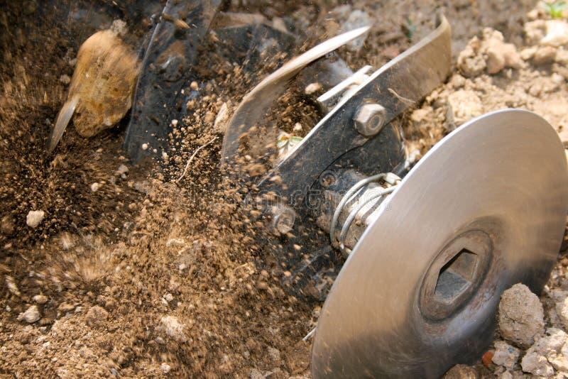 Machine die het land ploegen die stenen en overblijfselensprong maken royalty-vrije stock afbeelding