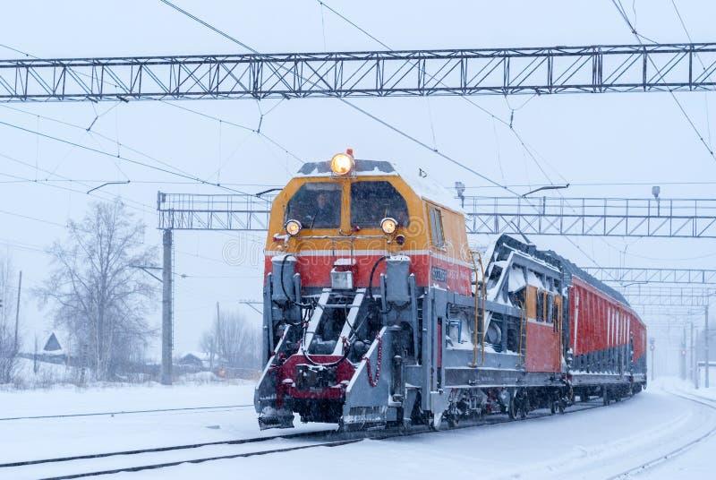 Machine ferroviaire de neige à la station pendant les chutes de neige photos stock