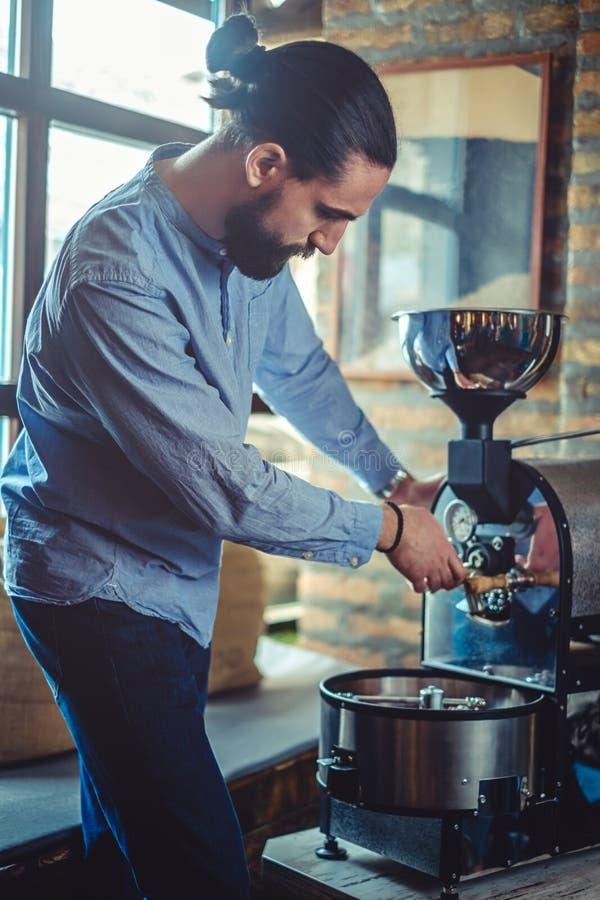 Machine fonctionnante de brûleur de café d'homme image stock