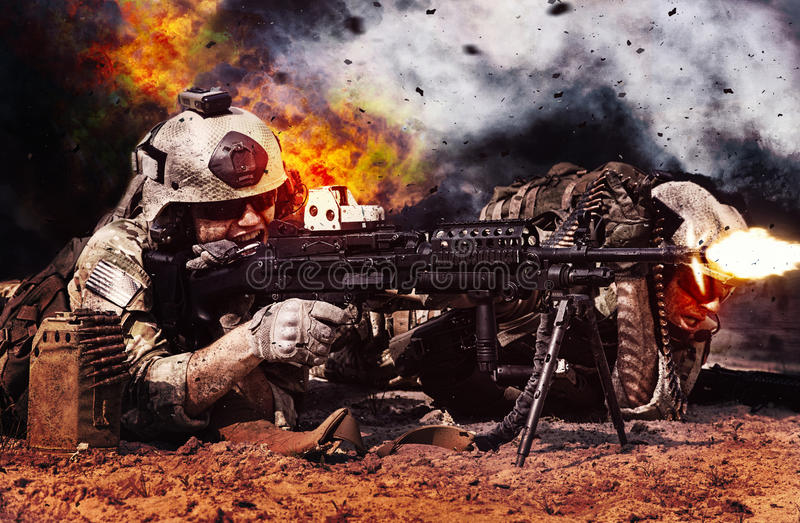 Machine gun crew in action. Two crewman of machine gun crew firing in the desert. Explosions fire shrapnel and clouds of black smoke billowing on background stock photo
