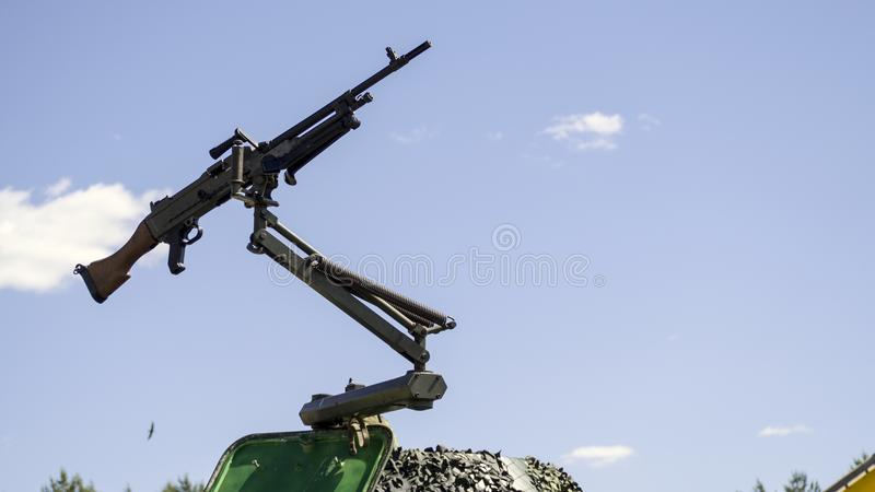 Machine gun mounted on military vehicle. Machine gun mounted on a military vehicle, army gun isolated on the blue sky background royalty free stock photography