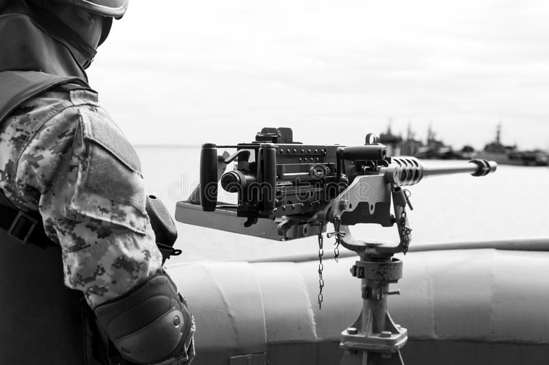 Machine gun and navy guard on the war ship. Machine gun and navy guard on war ship in black and white royalty free stock photography