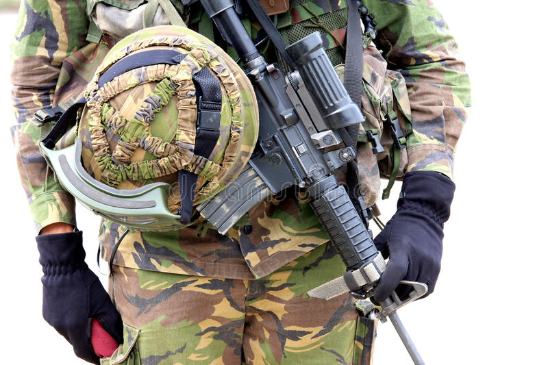 Machine gun and soldier helmet. A soldier of the Royal Netherlands Army in camouflage clothing is wearing his machine gun and helmet stock images
