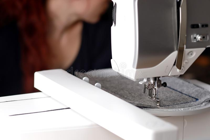 machine head of a modern sewing machine with embroidery unit stitching a blue frame on grey felt - background with redhead woman stock photography