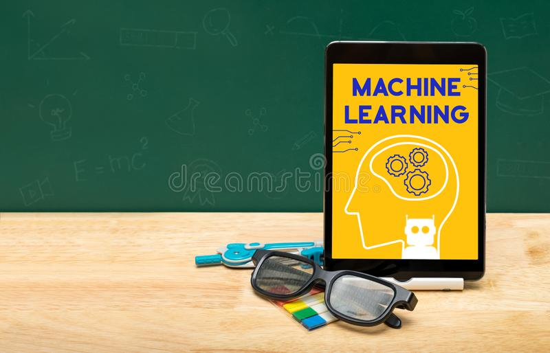 Machine learning bot on tablet with glasses on wood table and green blackboard with copy space for adding text.Artificial. Intelligence learning concept stock photography