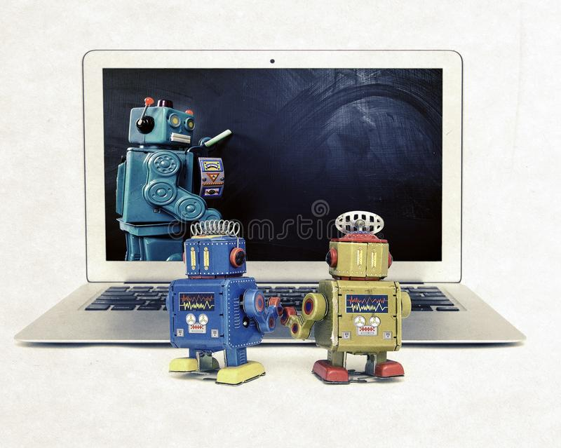 Machine learning concept with retro robots at a laptop computer stock photo