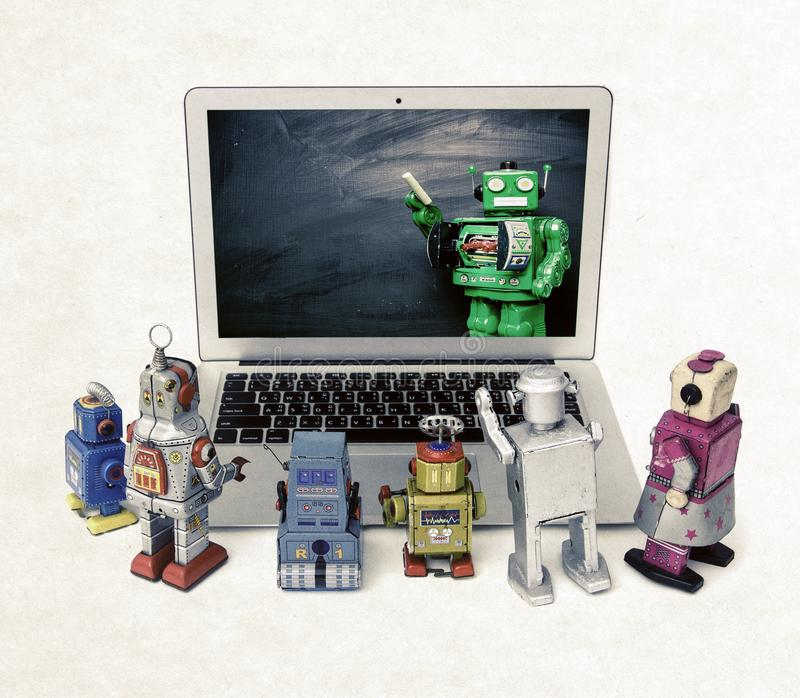 Machine learning concept with retro robots at a laptop computer. Isolated E= mc royalty free stock images